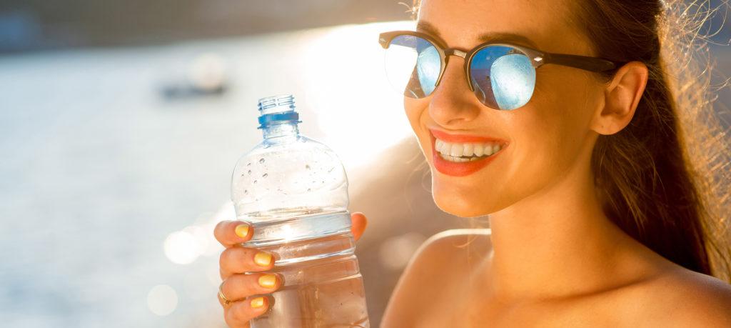 woman drinkin water on beach